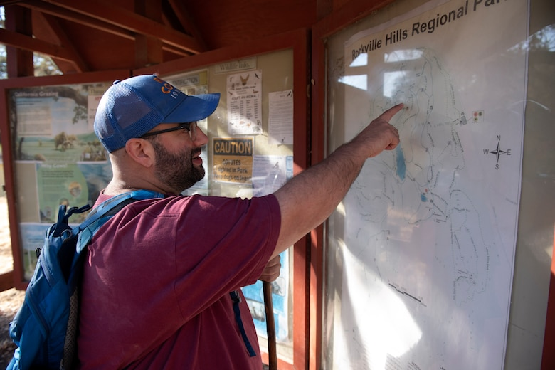 A man is touching a map near the beginning of a trail.