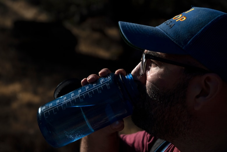 A man takes a drink of water during a hike.