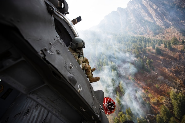 Crew members of the 211th Aviation Regiment conduct air support over the Neffs Canyon fire from a UH-60 Black Hawk helicopter in Salt Lake City, Utah, Sept. 20, 2020. The Black Hawk can drop 600 gallons of water over a wildfire at a time.