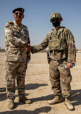 U.S. and Iraqi forces gather for the divestment of equipment from the U.S. government to the government of Iraq at a transfer point near Al Asad Air Base, Iraq, Oct. 15, 2020. Iraqi Maj. Gen. Saadoom Fouad, Q-West Air Base commander, received several containers consisting of air traffic control equipment that will build the Iraqi air force's capability to continue the fight to defeat the Islamic State of Iraq and Syria.(U.S. Army Reserve photo by Spc. Jorge Reyes)