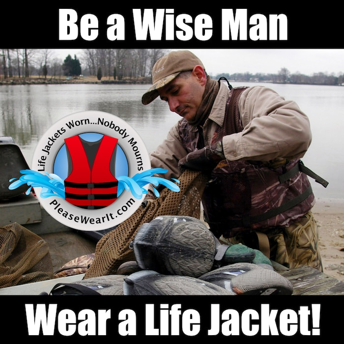 Duck Hunter wearing a life jacket as he prepares his decoys for hunting