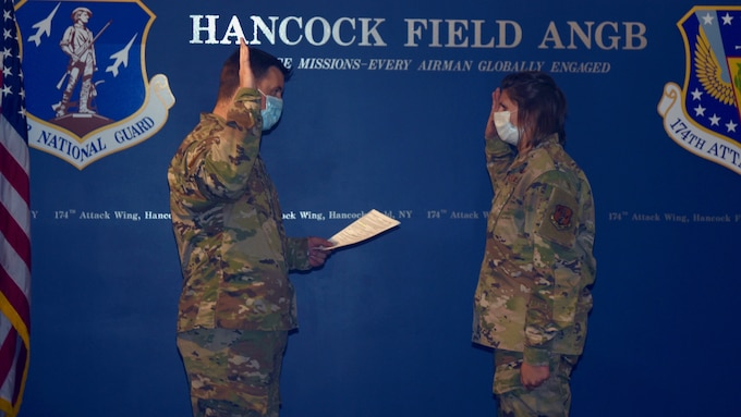 Capt. Devin Will (left) reads the Oath of Enlistment to Staff Sgt. Megan Fowler during a re-enlistment ceremony at Hancock Field Air National Guard Base September 28