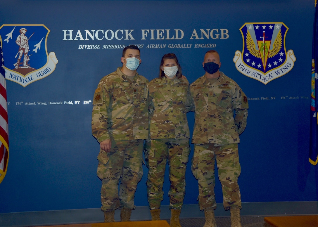 Capt. Devin Will (left), Chief Master Sgt. Michael Will (left), and Staff Sgt. Megan Fowler pose for a photo after Fowler's re-enlistment.