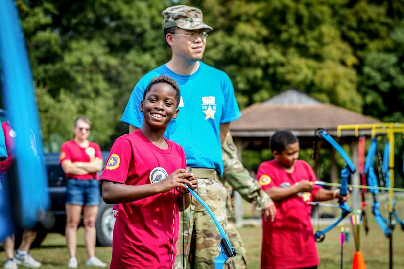 A youth holding an archery bow smiles for the camera as a soldier stands beside him on an outdoor field.