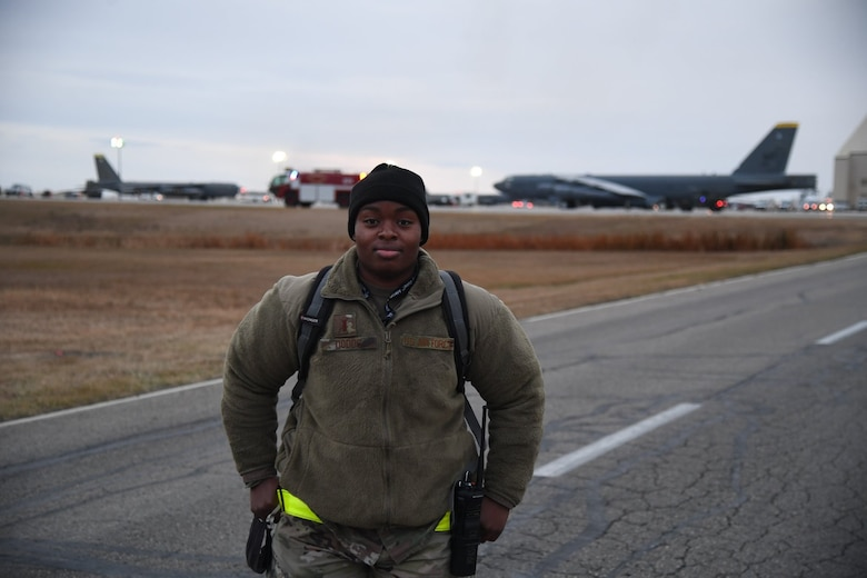 2nd Lt Dodds stands on the flightline in front of a backdrop of B-52s
