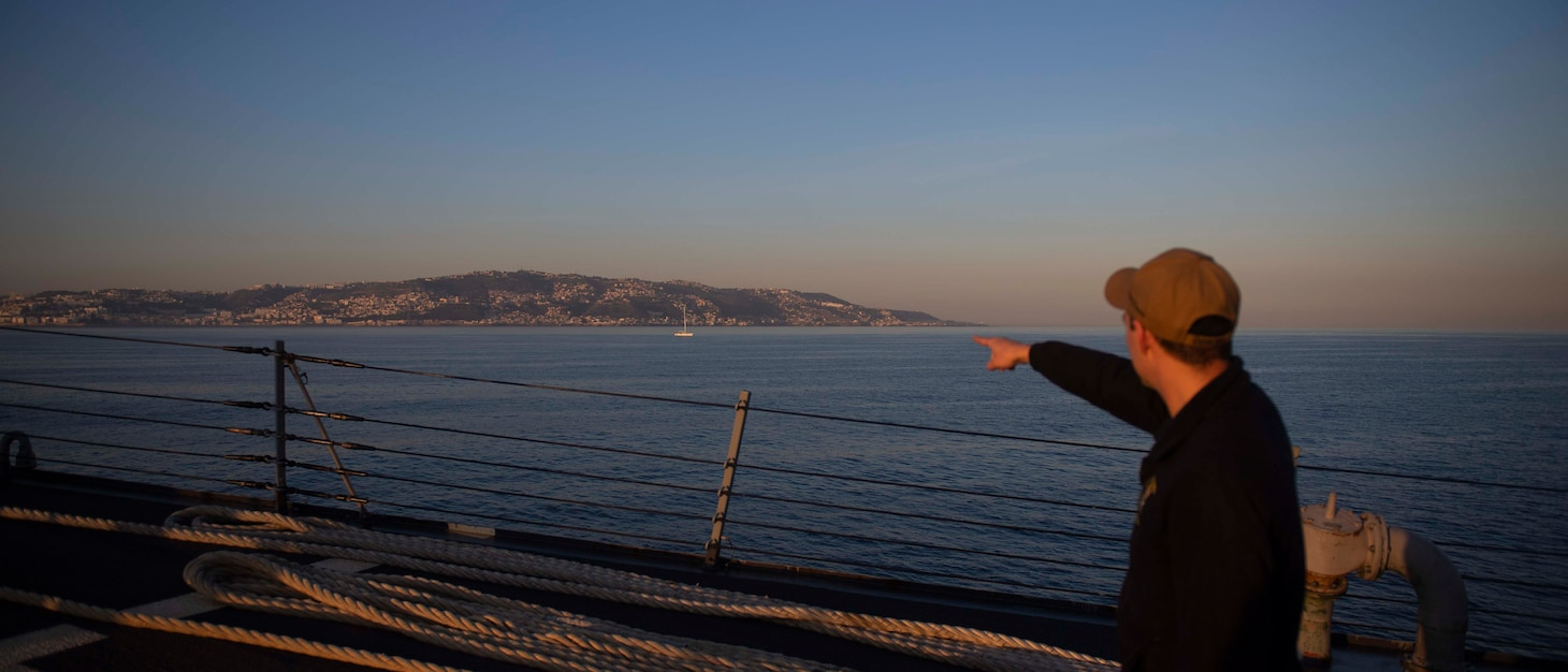 201018-N-KY668-1087 MEDITERRANEAN SEA (Oct. 18, 2020) Cryptologic Technician (Collection) 2nd Class Kyle Herring points to the skyline from the fo'c'sle aboard Arleigh Burke-class guided-missile destroyer USS Roosevelt (DDG 80) as the ship pulls into Algiers, Algeria for a scheduled brief stop for fuel, Oct. 18, 2020. Roosevelt, forward-deployed to Rota, Spain, is on its first patrol in the U.S. Sixth Fleet area of operations in support of regional allies and partners and U.S. national security interests in Europe and Africa. (U.S. Navy photo by Mass Communication Specialist Seaman Austin G. Collins/Released)