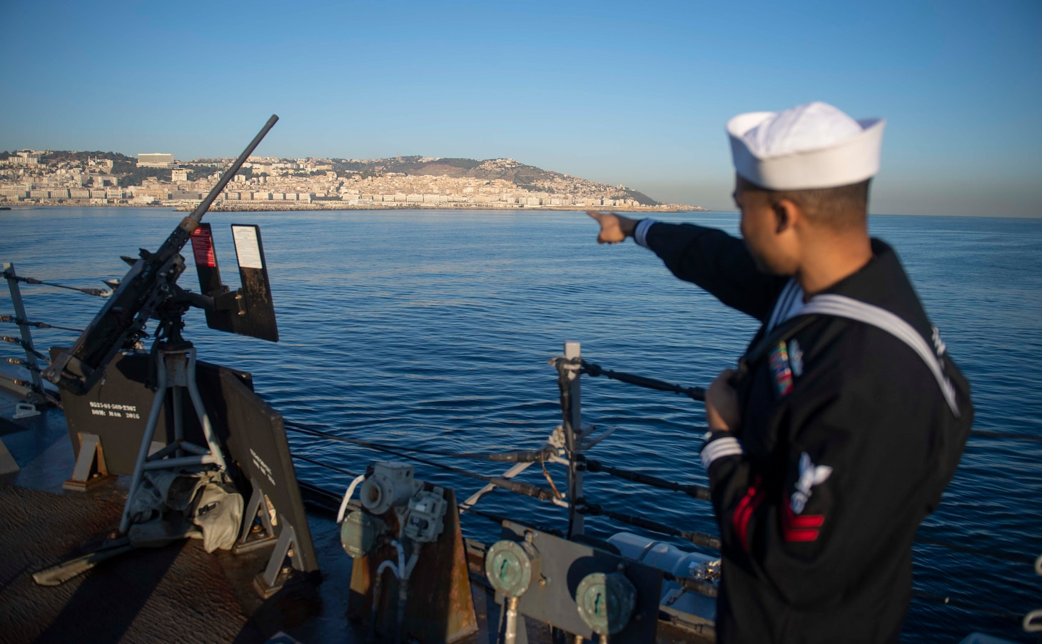 201018-N-KY668-1116 MEDITERRANEAN SEA (Oct. 18, 2020) Gas Turbine Systems Technician (Mechanical) 2nd Class Alva Johnson points to the skyline from the missile deck aboard Arleigh Burke-class guided-missile destroyer USS Roosevelt (DDG 80) as the ship pulls into Algiers, Algeria for a scheduled brief stop for fuel, Oct. 18, 2020. Roosevelt, forward-deployed to Rota, Spain, is on its first patrol in the U.S. Sixth Fleet area of operations in support of regional allies and partners and U.S. national security interests in Europe and Africa. (U.S. Navy photo by Mass Communication Specialist Seaman Austin G. Collins/Released)