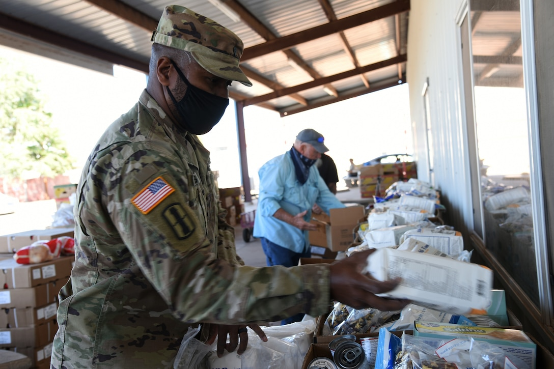 A service member wearing a face mask prepares boxes of groceries for delivery to residents.