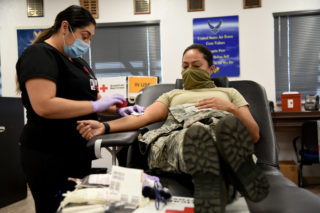 A medical tech wearing a face mask assists a soldier wearing a face mask while donating blood