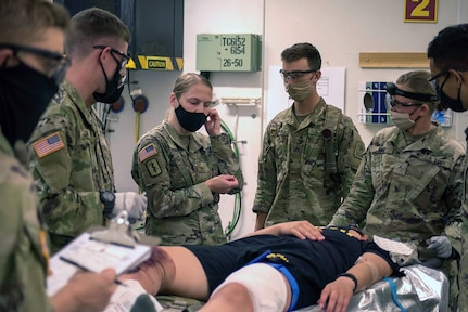 Students in the Combat Medic Specialist Training Program, or CMSTP, assess a simulated casualty during a field training exercise at Joint Base San Antonio-Camp Bullis.