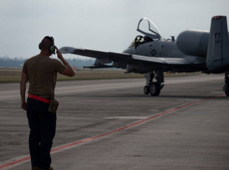 man salutes A-10 in background