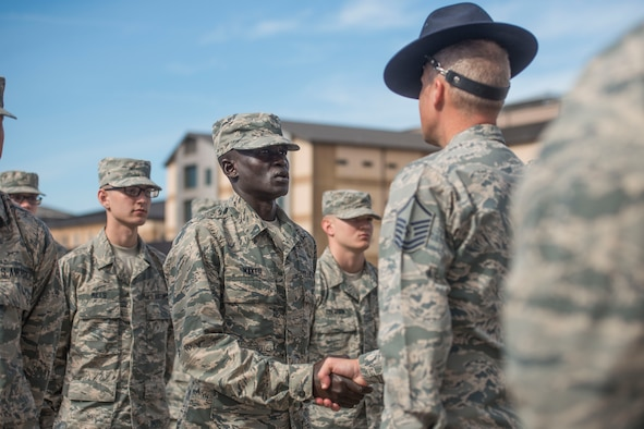 """Gour Maker, a trainee at Air Force Basic Military Training, receives an """"Airman's Coin"""" at the Coin Ceremony Feb. 1, 2018 outside the Pfingston Reception Center at Joint Base San Antonio-Lackland, Texas. During the BMT Coin Ceremony Trainees are given """"Airman's Coins' signifying the final transition from trainee to Airman. (U.S. Air Force photo by Airman 1st Class Dillon Parker)"""