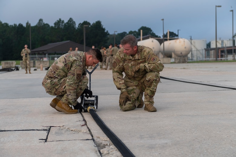 A photo of two airmen attaching a squeegee to a fuel hose.