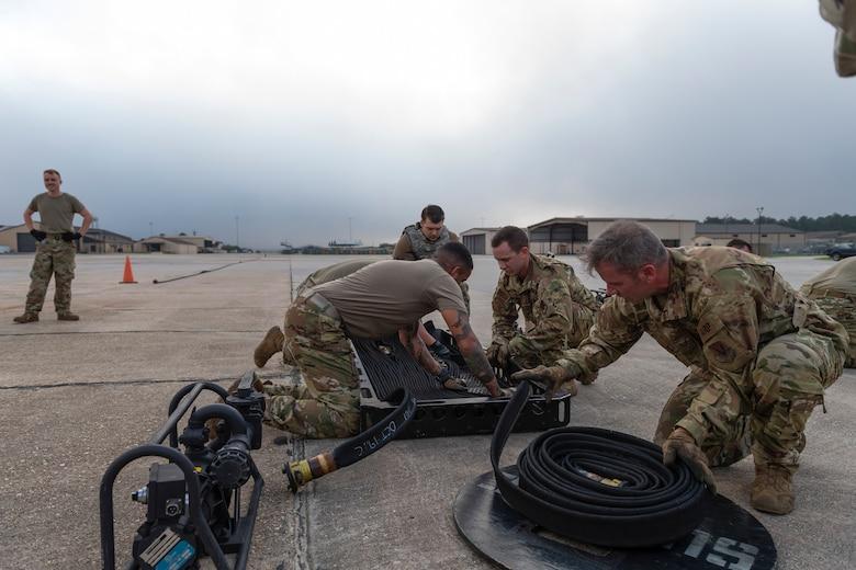 A photo of airmen unraveling a fuel hose into a basket.