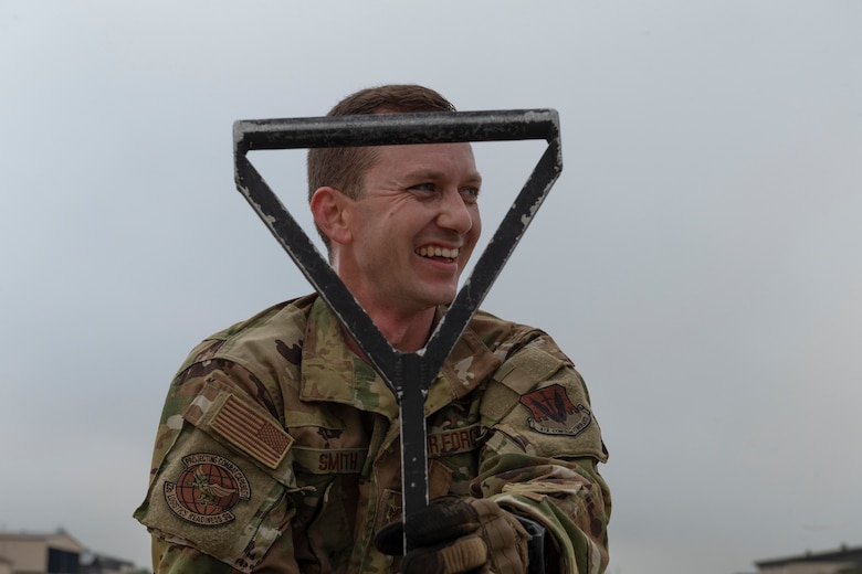 A photo of an airman smiling, holding a hose squeegee.