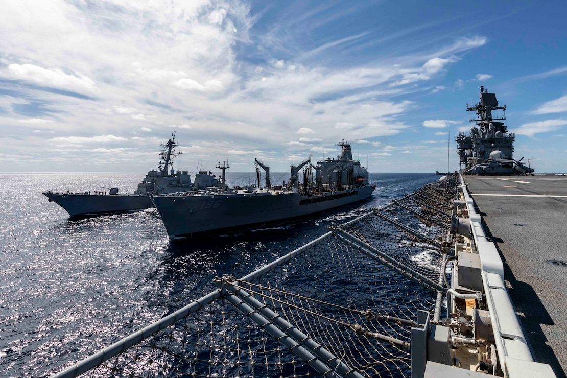 The Arleigh Burke-class guided-missile destroyer USS Arleigh Burke (DDG 51), left, and the Wasp-class amphibious assault ship USS Iwo Jima (LHD 7) come alongside the Henry J. Kaiser-class fleet replenishment oiler USNS Kanawha (T-AO 196) during a replenishment-at-sea during their Surface Warfare Advanced Tactical Training (SWATT), Oct. 15, 2020.