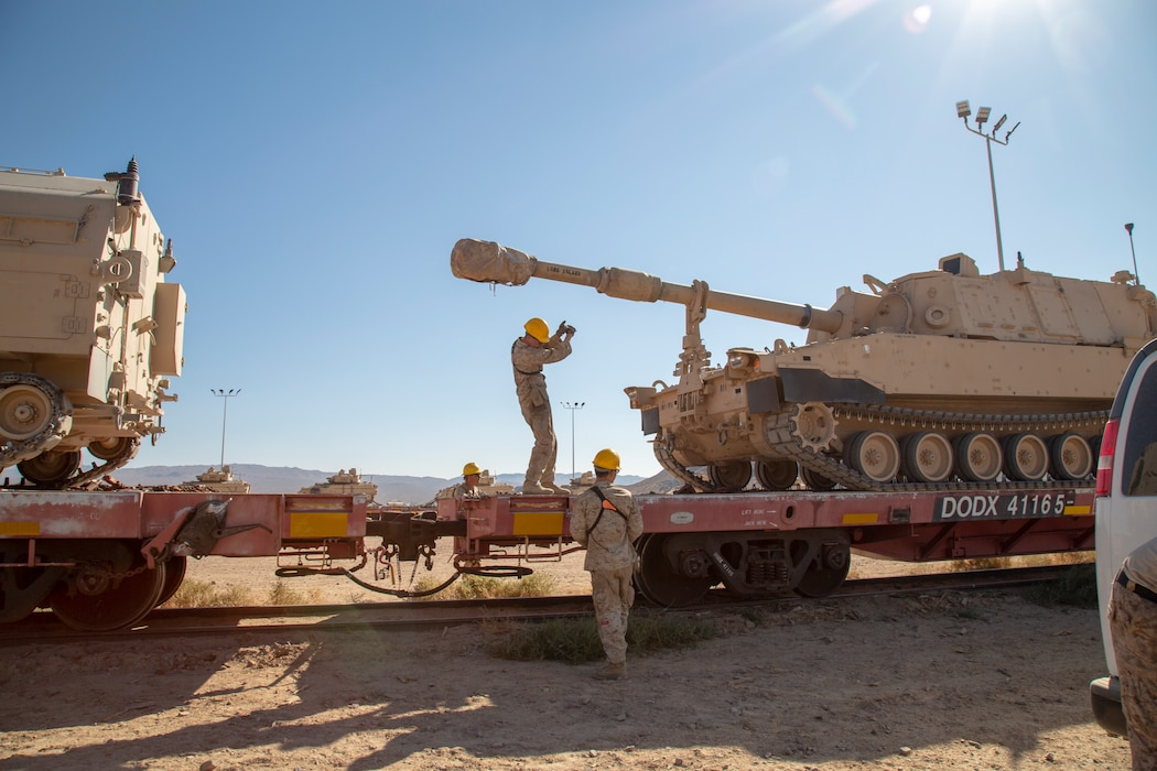 Marines work together to load a tracked vehicle onto a railcar as part of their training in Railhead Operations Group on the Yermo Annex aboard Marine Corps Logistics Base Barstow, California, Oct. 1.