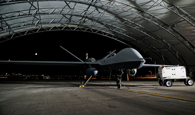 An MQ-9 Reaper sits under an aircraft sunshade with a bright light shining on it from the right side of the photo.