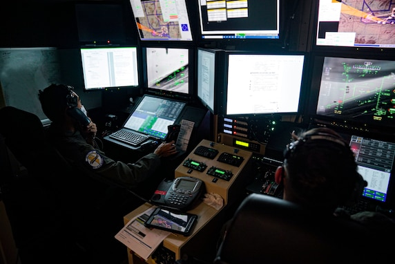 Two male Airmen in flight suits sit in an MQ-9 Reaper ground cockpit with papers and a phone between them. They are wearing a headset and are focused on the screens displaying flight information.