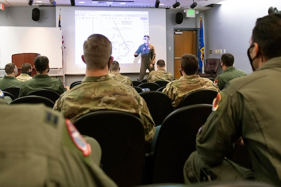 The backs of many Airmen sitting in chairs are towards the camera. The Airmen are facing an Airman presenter and a slideshow.