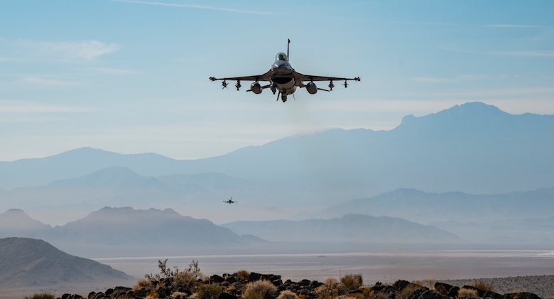 Two F-16s fly over mountain.