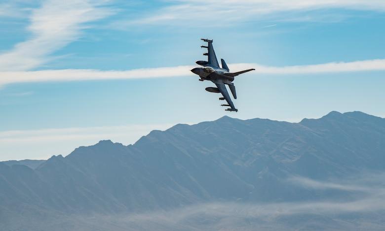 F-16 flies over mountain.