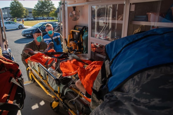 Image of medics loading an actor into an ambulance outside of the base theater.