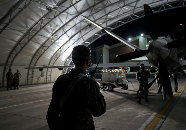 A male Airman faces the back of an MQ-9 Reaper Remotely Piloted Aircraft underneath an aircraft sunshade. The Airman is holding a walkie talkie in his right hand, and close to his face. The Airman's back is to the camera and his front is lit by a bright light. Four maintenance Airmen are working on the aircraft.