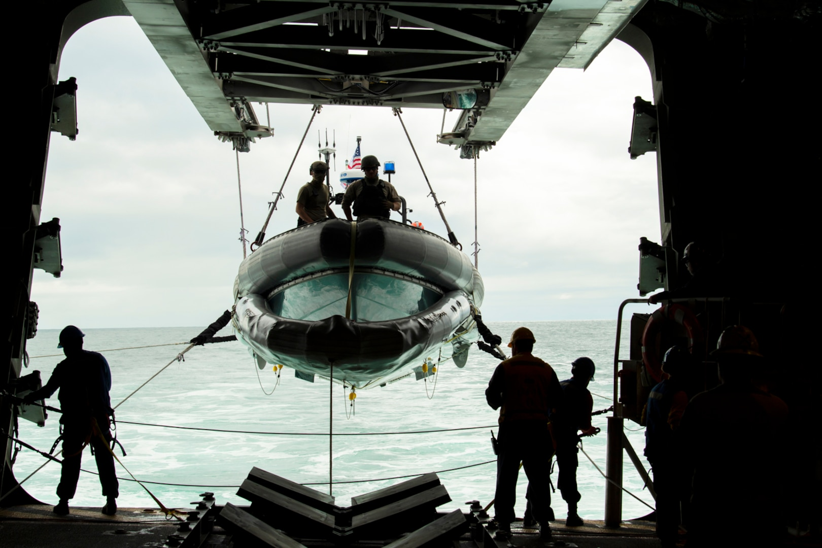 A small inflatable boat is lowered into the ocean.