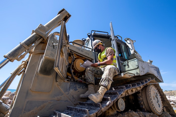 200910-N-RH019-0001 ROTA, Spain, (Sept. 10, 2020) Equipment Operator Constructionman Micah Slicer from Palm Coast, Fla. attached to Naval Mobile Construction Battalion (NMCB) 133 conducts daily maintenance on a D6T Dozer during coastal erosion restoration onboard Naval Air Station Rota, Sept. 10, 2020. CTF 68 provides explosive ordnance disposal operations, naval construction, expeditionary security, and theater security efforts in the 6th Fleet area of responsibility. (U.S. Navy photo by Mass Communication Specialist 2nd Class Sean Rinner/Released)
