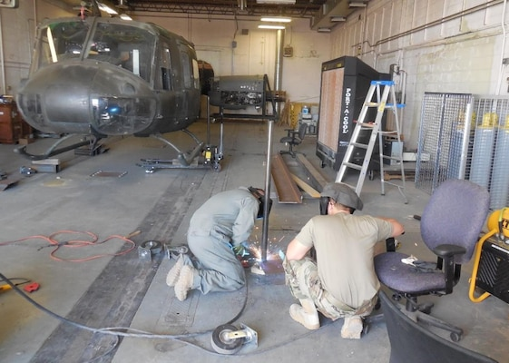 A member of the 210th RED HORSE team, left, welds a wheel caster in July 2020 while another member looks on. The wheel caster aided in the transport of the UH-1 helicopter airframe in the background. The airframe was relocated to the Defense Nuclear Weapon School training site on base to be used as a training aid.