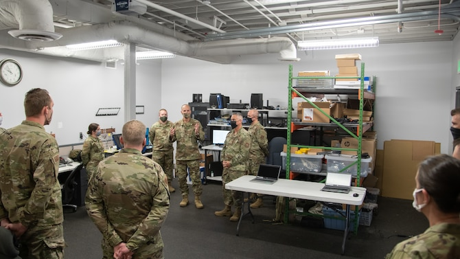 The 302nd Airlift Wing commander speaks to a group of Airmen from the 302nd Communications Flight surrounded by equipment in a room.