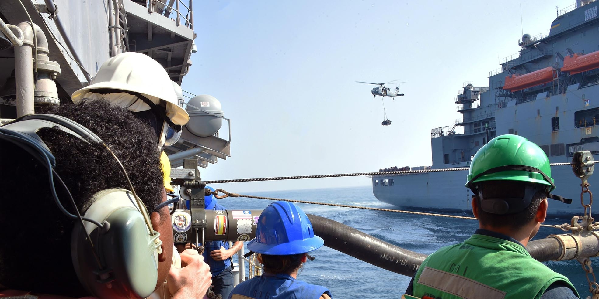 An MH-60S Seahawk helicopter transports cargo from the Military Sealift Command dry cargo and ammunition ship USNS Matthew Perry (T-AKE 9) to the guided-missile cruiser USS Philippine Sea (CG 58) during a vertical replenishment-at-sea in the Arabian Sea, Oct. 7.