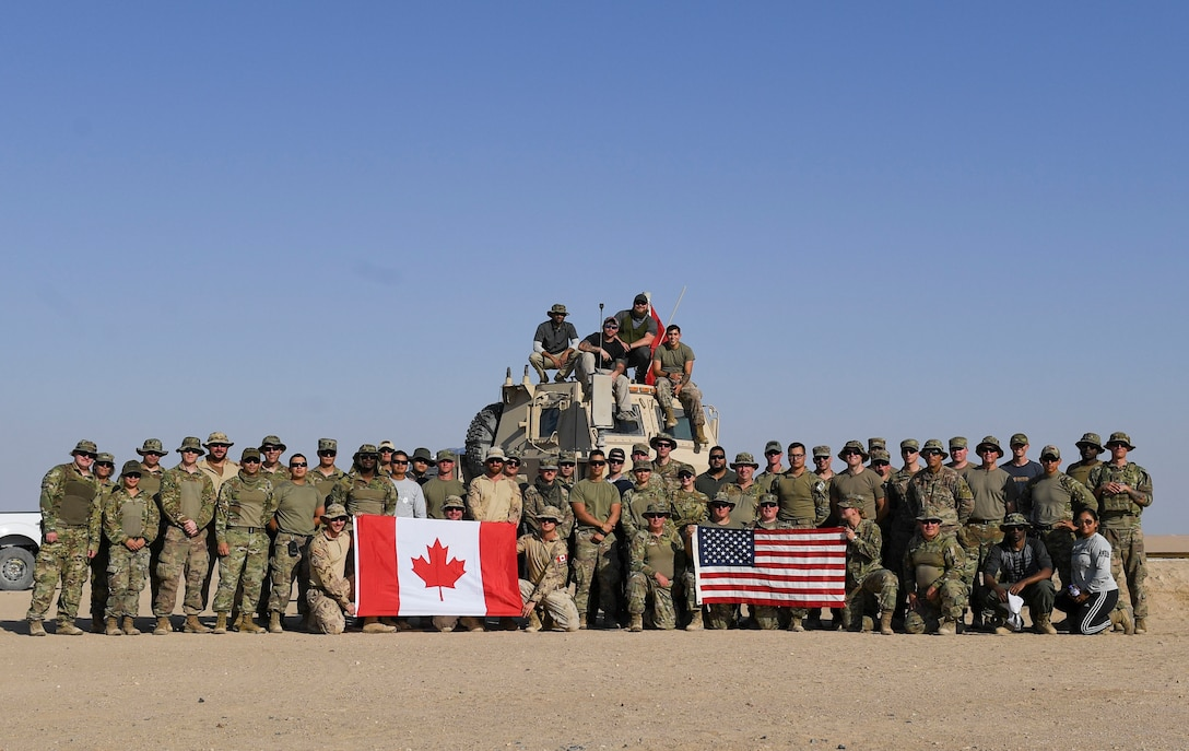 U.S. Army Soldiers, U.S. Air Force Airmen and Canadian Armed Forces members pose for a photo at the Udairi Range Complex, Kuwait, Oct. 12, 2020. The range day event was an opportunity to maintain key working relationships with mission partners in the joint and multi-national Special Operations Command Central network. (U.S. Air Force photo by Senior Airman Monica Roybal)