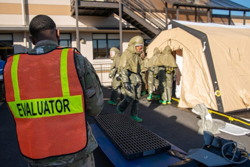 "A man wearing a vest bearing the word ""evaluator"" watches several service members."