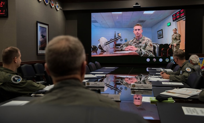 ACC 4 Star General sitting at table with screen in front of him
