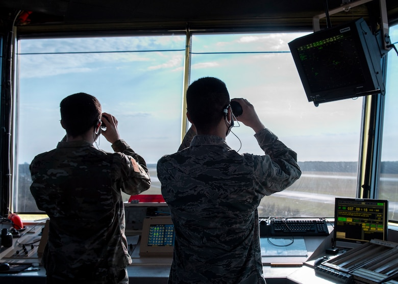Senior Airman Nathan Puffinberger, 4th Operations Support Squadron air traffic control journeyman (left), and Airman 1st Class Noah Romero, 4 OSS ATC apprentice (right), use binoculars to locate distant aircraft, check on landing gear and look for birds at Seymour Johnson Air Force Base, North Carolina, Oct. 2, 2020.