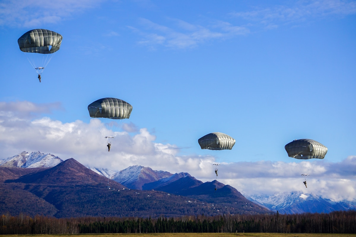 Four parachutists jump from an aircraft with mountains as a backdrop.