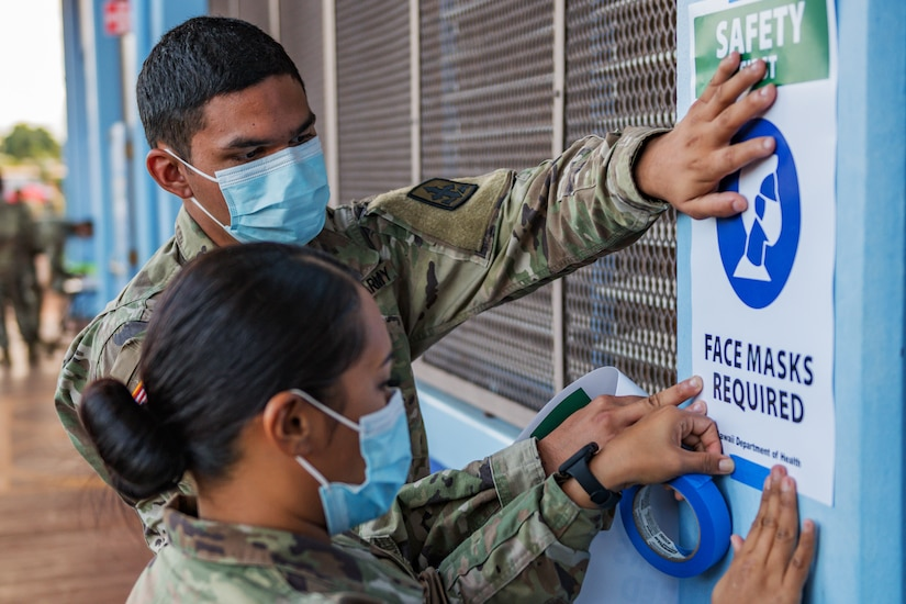 Two guardsmen -- one man and one woman -- wear face masks and tape signs requiring face masks to the outside of a building.