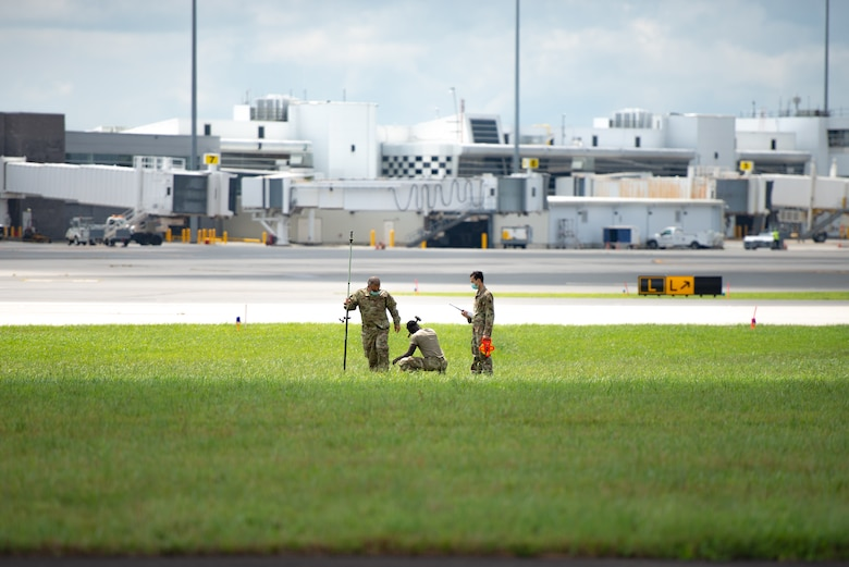 A photo of Staff Sgt. Kevin Tan, Staff. Sgt. Derick N. Donkor and Tech. Sgt. Peter G. Kurt marking specific locations to put stakes in the ground on the 177th Fighter Wing runway.