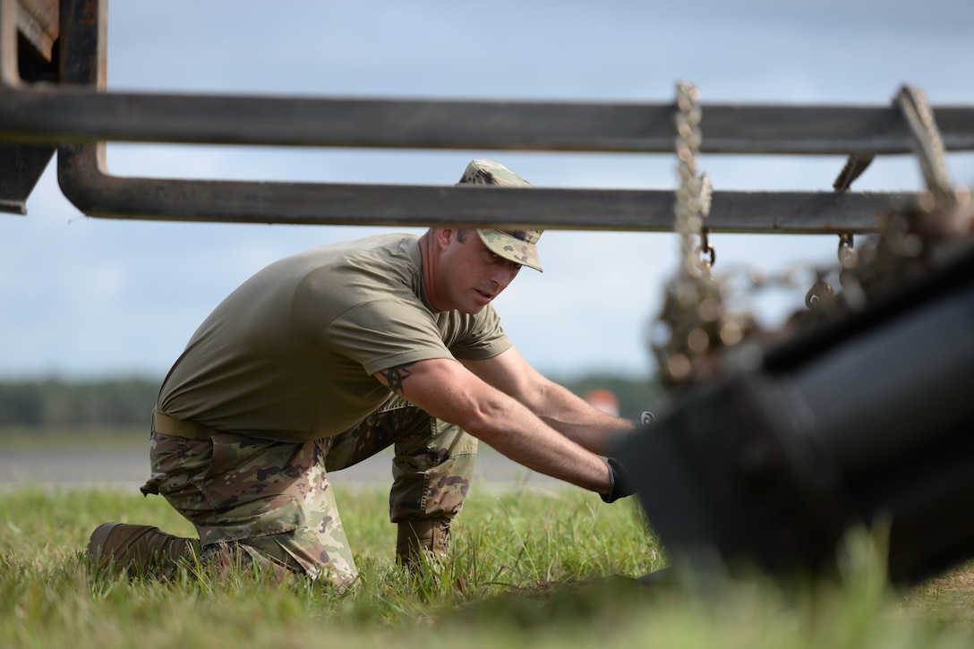 A photo of Tech. Sgt. Anthony J. Foster assisting the installation of a mobile arrestor system.
