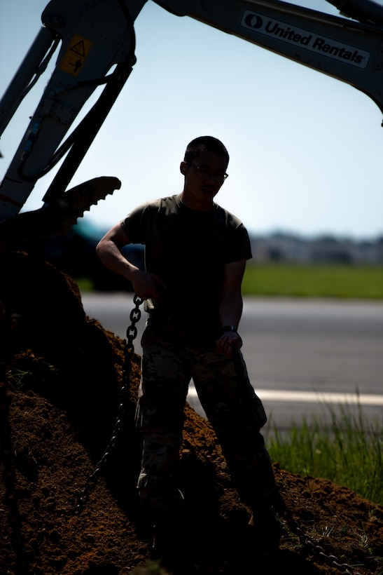 A photo of Airman 1st Class Alejandro Ng Feng fastening a chain.