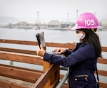 Anh Tran with Code 105, Radiological Controls, uses a tablet while conducting work on the Puget Sound Naval Shipyard & Intermediate Maintenance Facility waterfront as part of the command's Mobile Workforce Enablement initiative, which increases efficiency, reduces delays and puts valuable information within reach of employees, wherever they are working. (PSNS & IMF photo by Wendy Hallmark)