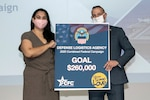 Viju Dilley, DLA's CFC loaned executive, and Jeff Zotolla, DLA Finance vice director and vice chair for DLA's campaign, pose with a sign depicting the agency's 2020 goal of $260,000 during a kickoff ceremony at the McNamara Headquarters Complex on Fort Belvoir, Virginia, Oct. 20, 2020. Photo by Teodora Mocanu
