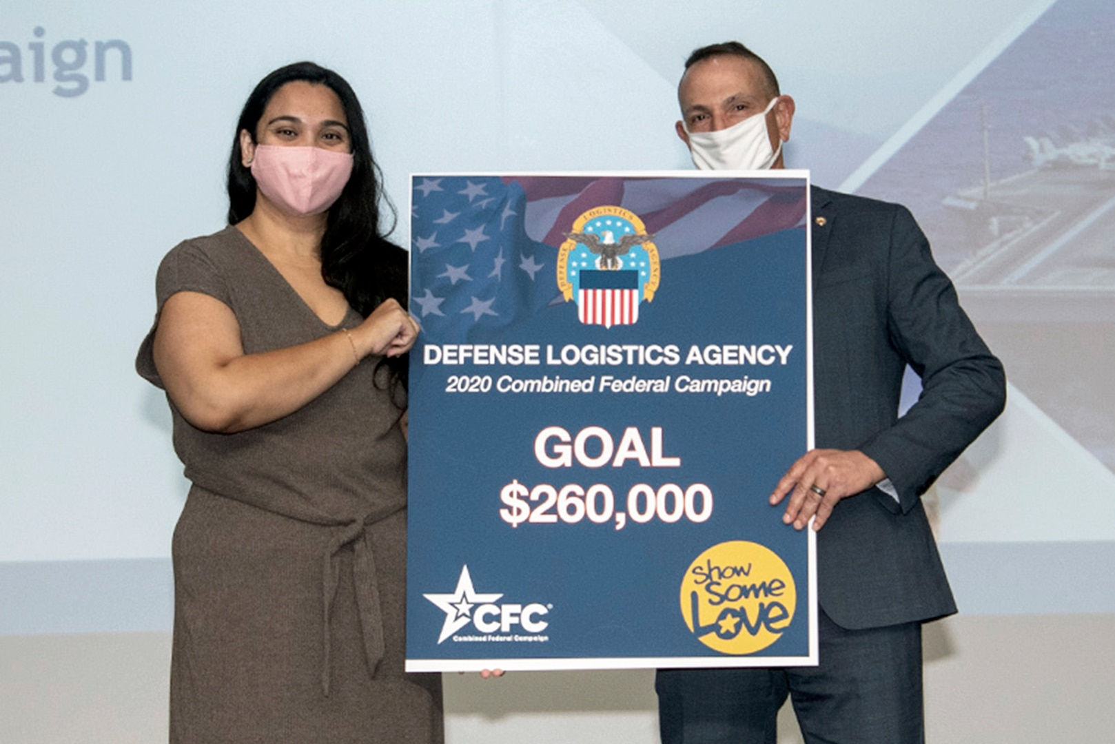Man and woman wearing face masks over their mouth and nose hold a blue sign that reads Defense Logistics Agency 2020 Combined Federal Campaign Goal $260,000.