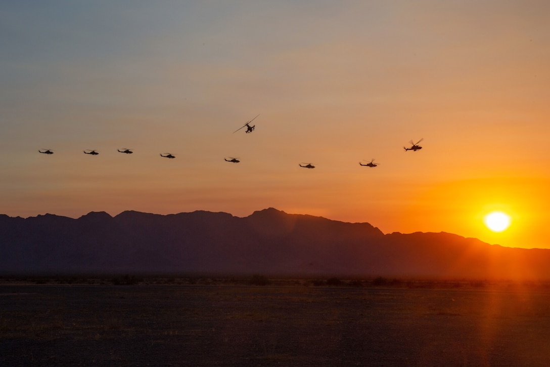 A group of helicopters fly over the mountains with the sun in the background.