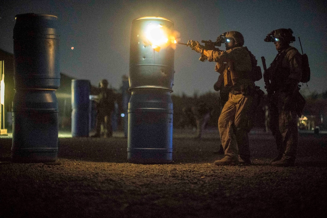 A Marine fires a weapon as another Marine watches.