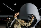 An MQ-9 Reaper maintainer checks the front nose of an MQ-9 during a preflight inspection at night.