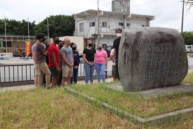国道329号線沿いの草刈り作業に参加した第9工兵支援大隊の海兵隊員に、日本軍屋嘉捕虜収容所跡の碑の説明をする米海兵隊基地キャンプ・ハンセンの嘉陽渉外官