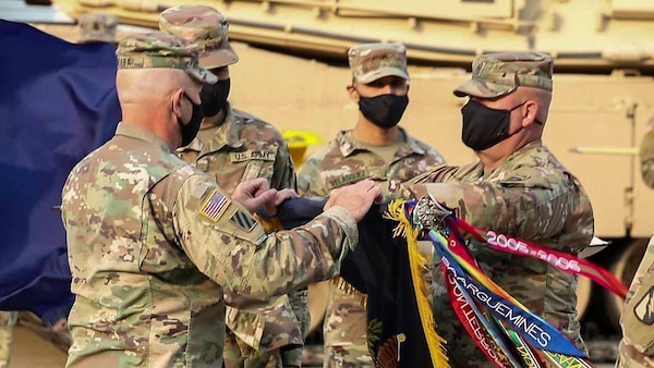 """Lt. Col. Rodney Seaba, left, commander of the Kansas Army National Guard's 2nd Combined Arms Battalion, 137th Infantry Regiment, and Command Sgt. Maj. Paul Purdham, right, case the regimental colors of the Kansas Army National Guard's 2nd CAB, 137th Infantry Regiment Oct. 17. The ceremony was held to redesignate the 2nd CAB, 137th Infantry Regiment, """"First Kansas,"""" as the 1st Battalion, 635th Armor Regiment, in accordance with a 2012 Army chief of staff directive."""